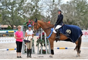 ©ESI Photography Callan Solem, aboard her fifth-place horse VDL Wizard, accepts winning honors for her ride on VDL Torlando in the $25,000 SmartPak Grand Prix, presented by Zoetis, at HITS Ocala.