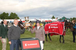 Christine McCrea lifts her trophy for winning the $33,000 Scotiabank Cup with Mike Jackson, Managing Director, Scotia Capital. Photo © Spruce Meadows Media Services.