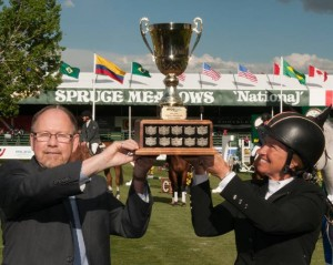 Beezie Madden and Derek Neldner, Managing Director, Global Investment Banking, RBC Capital Markets, lift the winning trophy. Photo © Spruce Meadows Media Services.