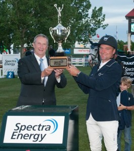 Darragh Kerins is congratulated with a trophy by Doug Bloom, President Canadian LNG, Spectra Energy, for his win in the $35,000 Spectra Energy Cup 1.60m. Photo © Spruce Meadows Media Services.