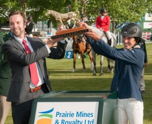 Lauren Tisbo and Sean McCaughan, Sr. Vice President of Prairie Mines & Royalty LTD, lift the trophy to celebrate her first win in the International Ring.