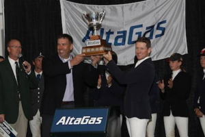 McLain Ward and David Harris, President, Gas & Power, AltaGas, lift the winning trophy. Photo © Spruce Meadows Media Services.