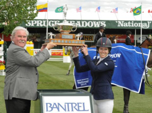 Christine McCrea raises her winning trophy in the $33,000 Bantrel Cup with Darrell Donly, President of Bantrel Co. Photo © Spruce Meadows Media Services.