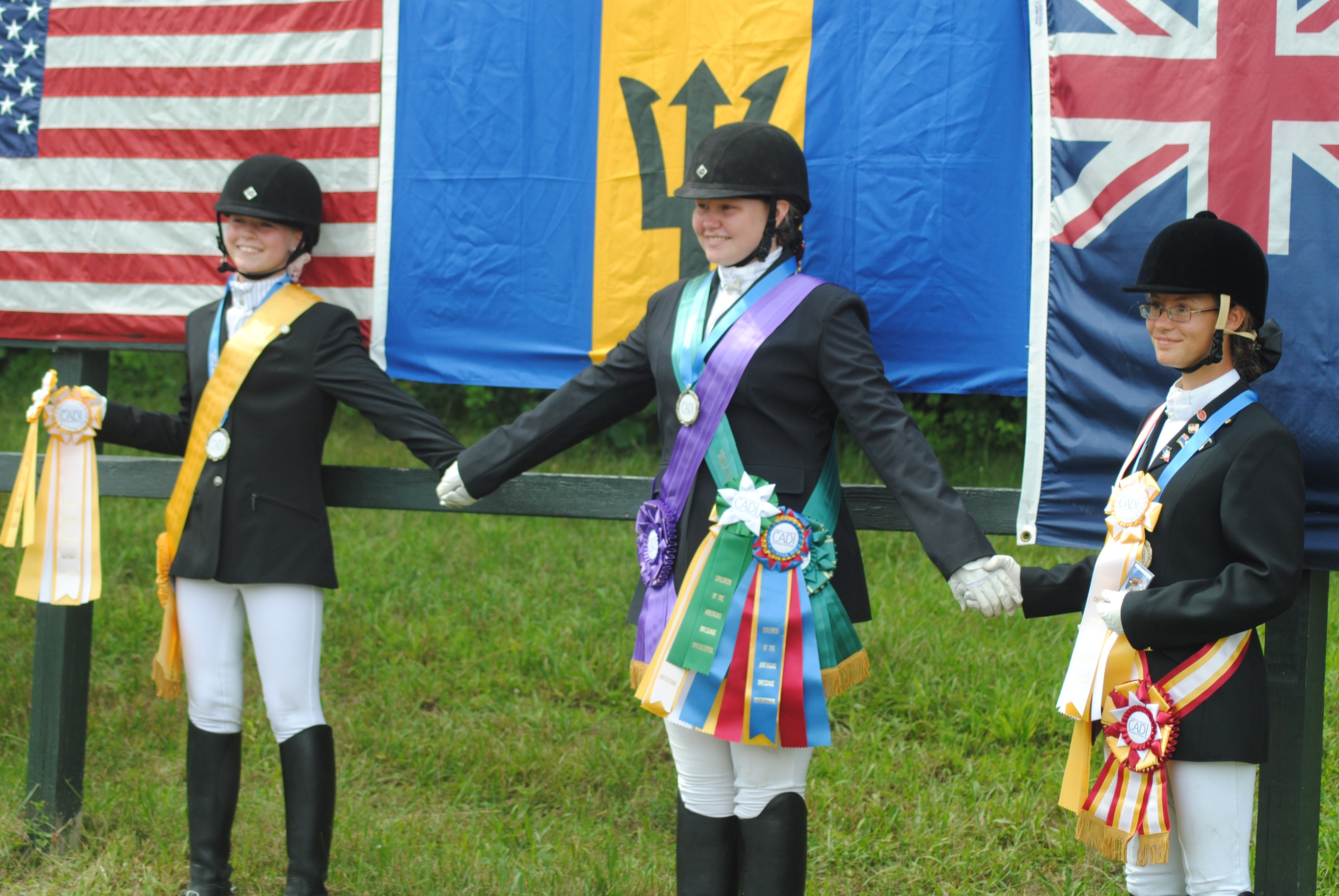 From left to right, Caroline McConnell of the USA, Kenzie Manning of Barbados and Anja van Genderen of the Cayman Islands celebrate their new friendship and third place finish in the team competition. While CADI is a competition, one of the big goals is for the riders to learn about one another's cultures.