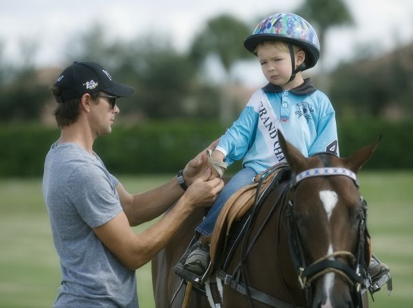 Professional polo player Jeff Hall helping son Luke with his mallet strap before the start of the Pro Leadline. Photo by Scott Fisher