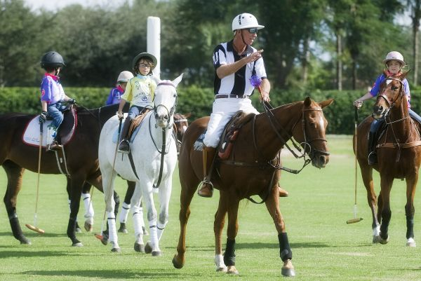 Umpire Scott Campbell leads Lorenzo Ramirez of Polo School Yellow and other Walk Alone participants out onto the field. Photo by Scott Fisher