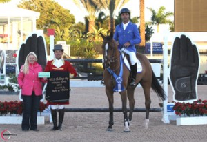 Alvaro 'Doda' Miranda, mounted on AD Uutje, is presented with a $3,000 bonus from Jennifer Ward on behalf of SSG Gloves for wearing SSG 'Digitals' on his way to victory in the $34,000 WEF Challenge Cup Round II at the 2014 FTI Consulting Winter Equestrian Festival in Wellington, FL. Photo by Sportfot