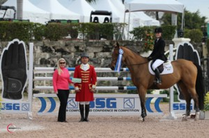 "Chloe D. Reid topped a 10-horse jump-off riding King of Hearts to win the $10,000 Junior Jumper Classic and a $1,000 bonus in the SSG Gloves ""Go Clean for the Green"" promotion.  Presenting on behalf of SSG Gloves is Jennifer Ward with ringmaster Gustavo Murcia. Photo by Sportfot"