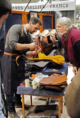 Photo 53 – A number of saddle makers were present in the Royal shopping area. Here the saddle maker from Antarés shows a visitor his work. Photo by Sarah Miller/MacMillan Photography