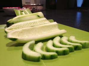 Slicing and seeding a cucumber in half moon shapes.