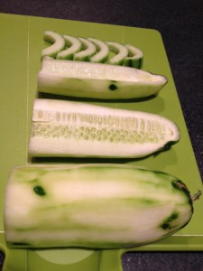slicing and seeding a cucumber in half moon shapes, showcasing exactly how it's done.