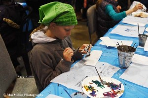 35-A little girl exercises her artistic expression as she paints a small Breyer model in the kid's activity area.