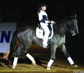 """Jeannette Sassoon and her blind dressage horse Valiant performed a moving demonstration at the Reining World Freestyle Championship, part of the Ariat Kentucky Reining Cup, which took part during Rolex in Lexington, Kentucky. (Check out the feature story on Jeannette and Valiant in the June issue of Sidelines). In addition to their demonstrations and upcoming documentary, Jeannette wrote a song for Valiant, """"Follow My Heart,"""" which has been recorded by new country Nashville artist Veronica Taylor. We can't wait to hear the song on the radio.                                   Photo by Mandy Su – amsphotography.com"""