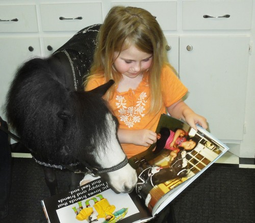 Therapy horse Magic reads with Taylor Kimmel, a survivor of Briarwood Elementary School in Moore, Oklahoma. Taylor's father, Toby Kimmel, was driving to the school to pick up his first grader when he saw the tornado destroy the school. Just hours after this photo was taken Taylor was in a storm shelter and became a two-time tornado survivor.