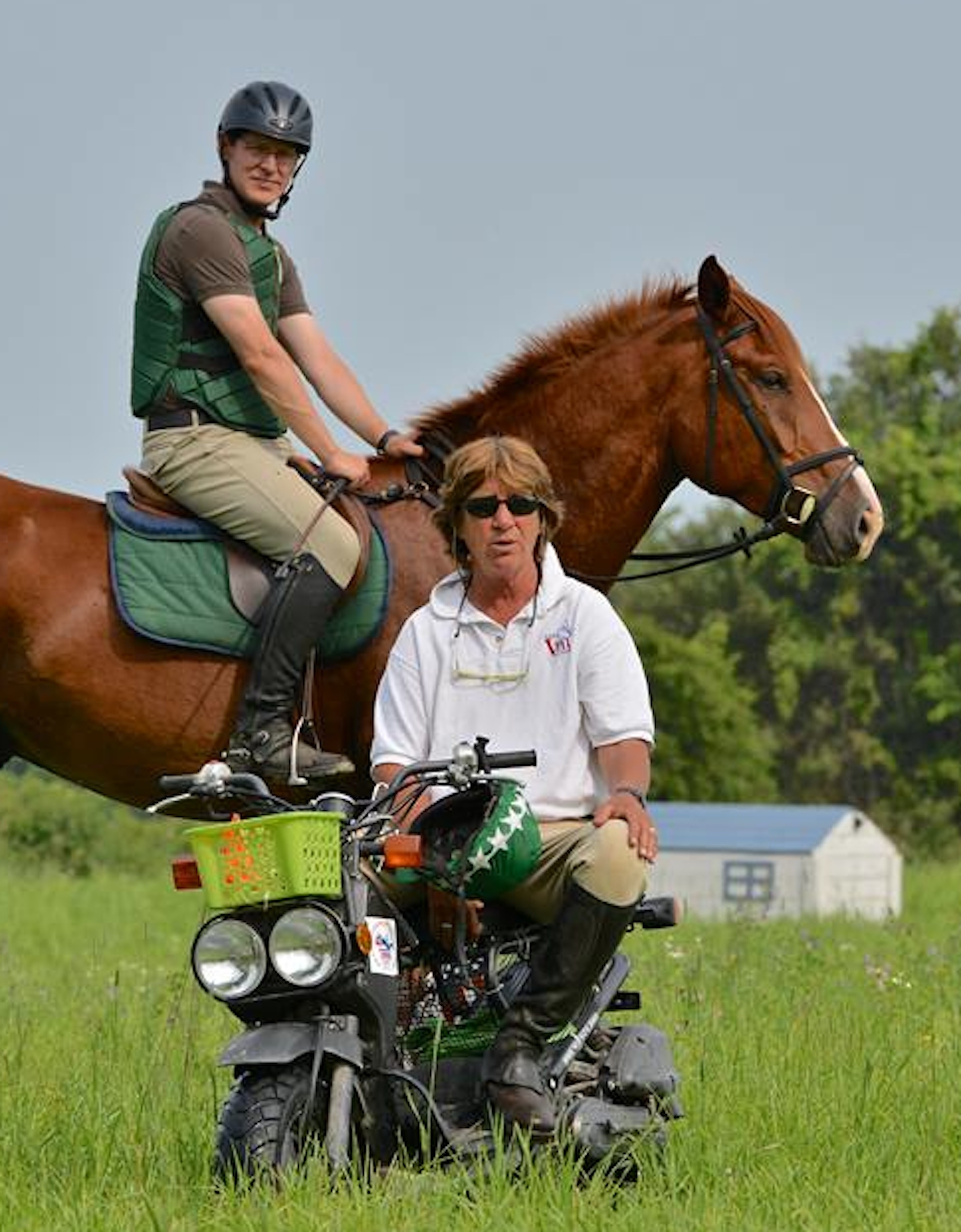 Cathy teaching on the cross-country course at Sprucehaven Farm, Canada, during her 2014 eventing clinic. Participant Andrew Pocock stands by. (Photo by Ian Woodley)