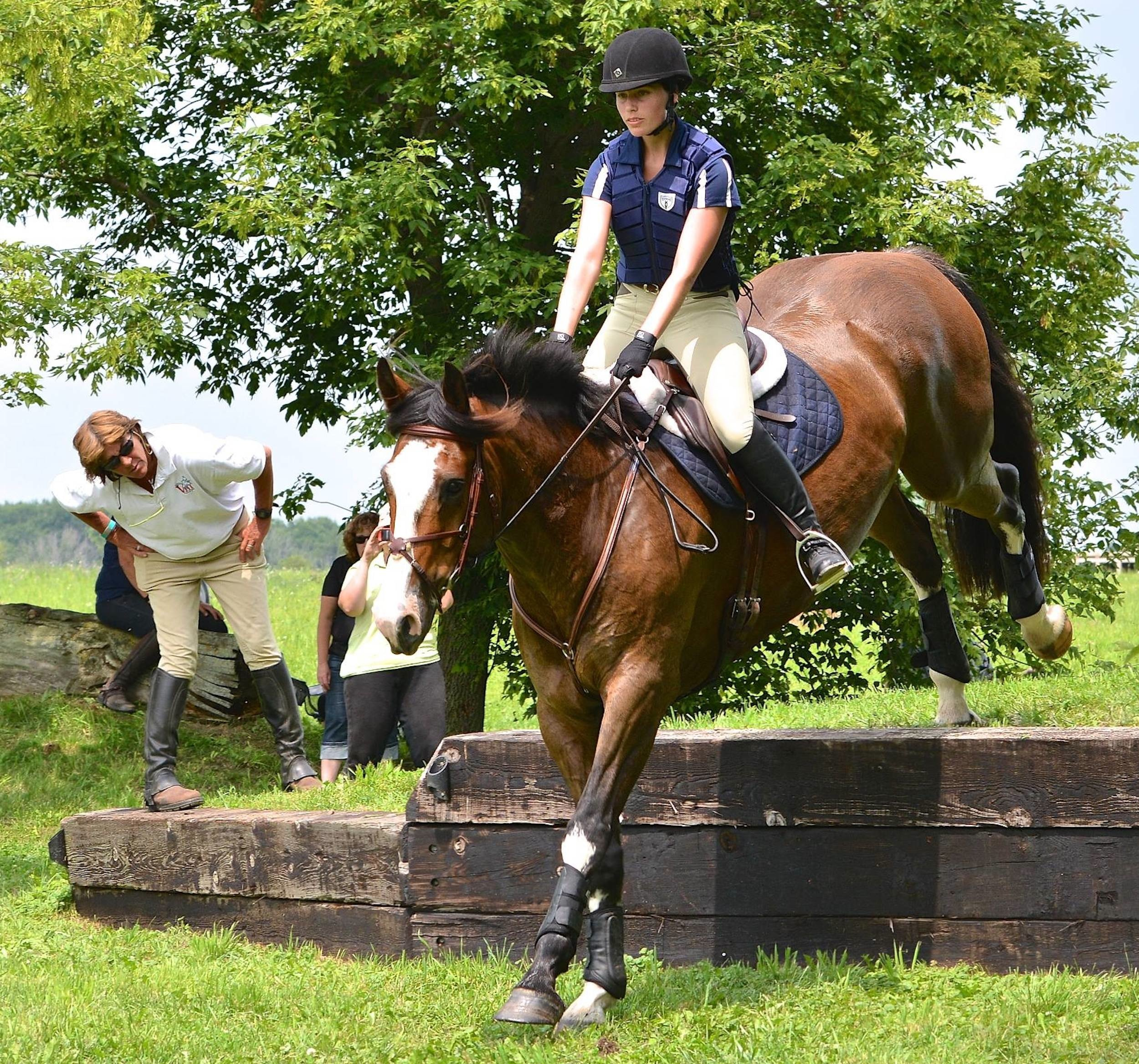 Cathy watches closely as a rider in Sprucehaven Farm's 2014 eventing clinic (Canada) negotiates a drop. (Photo by Ian Woodley)