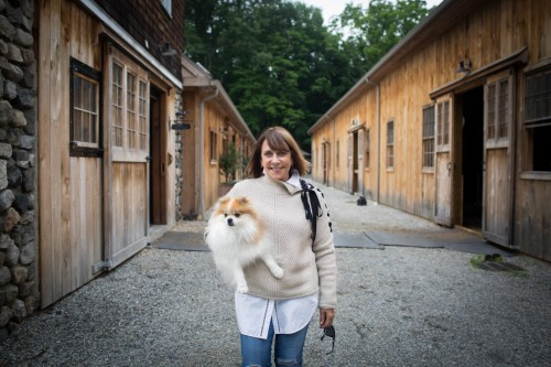 Gretchen Hunt, owner of Hunt Ltd., with Pomeranian, Nugget, in a Veronica Beard side lace crew neck sweater, lace trim Vince cotton shirt and AG Jeans at Findlay's Ridge at SweetWater Farm in North Salem, New York. Photo by Brittnay Brett