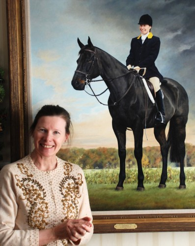Anita Baarns stands in front of her self-portrait featuring her horse Conrad
