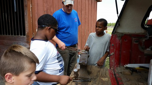Kids in the Detroit Horse Power program learning about farrier work. Photo by David Silver