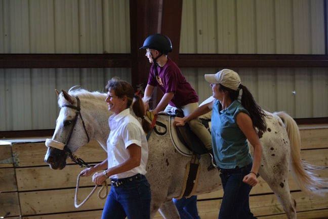 A young rider enjoys trotting with Loudoun Therapeutic Riding volunteers. Photo courtesy of Loudoun Therapeutic Riding