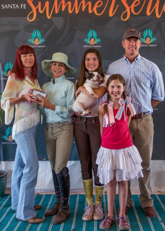 Henri is thrilled that her grandchildren love horses. From the left, Phyllis Gonzales, HIPICO leadership, Henri, granddaughters Blythe Bouza holding Eloise and Greer Bouza and their father Kevin Bouza at the HIPICO Santa Fe 2015 Summer Series. Photo by Adrian Wills