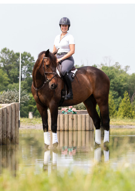Lillian Heard and LLC Barnaby standing in the water on cross-country.